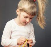 Menina bonita que rosqueia grânulos em um fio amarelo Foto de Stock Royalty Free