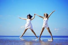 Menina bonita que salta na praia Fotos de Stock Royalty Free
