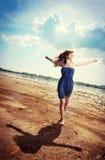 Menina bonita que salta na praia Imagens de Stock Royalty Free
