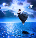 Menina bonita que salta no céu nocturno azul Fotografia de Stock Royalty Free