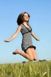 Menina bonita que salta no campo Foto de Stock Royalty Free