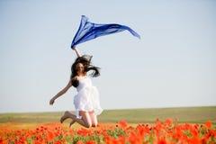 Menina bonita que salta no campo da papoila imagem de stock royalty free