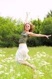 Menina bonita que salta no parque Foto de Stock Royalty Free
