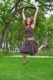 Menina bonita que salta no parque Fotos de Stock