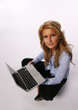 Menina bonita que senta-se com computador portátil Imagens de Stock