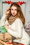 Menina bonita que senta-se com presentes do Natal Imagens de Stock Royalty Free