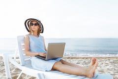 Menina bonita que senta-se com um portátil em uma espreguiçadeira, uma mulher que trabalha em férias, procura de emprego imagens de stock