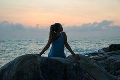 A menina bonita que senta-se em pedras e que olha em uma distância, menina no por do sol para meditar no silêncio, corpo bonito C fotos de stock royalty free