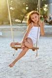 Menina que senta-se em um balanço Fotos de Stock Royalty Free