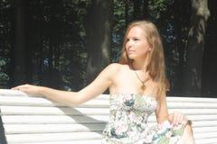 Menina bonita que senta-se em um banco Foto de Stock Royalty Free