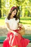 Menina bonita que senta-se em um banco e que guarda uma cesta com appl Imagem de Stock
