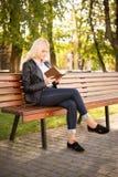 Menina bonita que senta-se em um banco e que lê um livro Foto de Stock