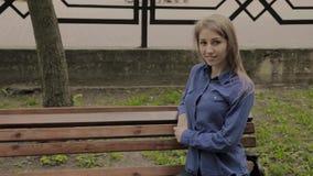 Menina bonita que senta-se em um banco em um parque da cidade vídeos de arquivo