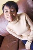Menina bonita que senta-se em um sofá fotos de stock royalty free