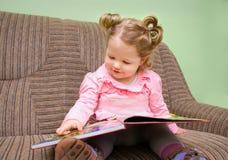 Menina bonita que senta-se em um sofá e que olha um livro ilustrado das crianças Imagens de Stock Royalty Free