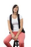 Menina bonita que senta-se em um tamborete fotos de stock
