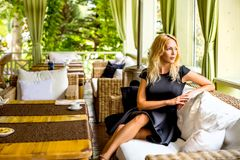 Menina bonita que senta-se em um treinador no café Fotografia de Stock Royalty Free