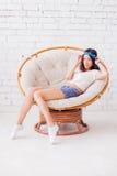 Menina bonita que senta-se em uma cadeira Fotografia de Stock
