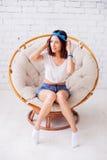Menina bonita que senta-se em uma cadeira Imagem de Stock
