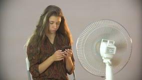 A menina bonita que senta-se em uma cadeira perto do fã e escreve sms no móbil filme