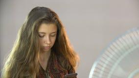 A menina bonita que senta-se em uma cadeira perto do fã e escreve sms no móbil vídeos de arquivo