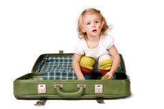 Menina bonita que senta-se em uma mala de viagem Fotos de Stock