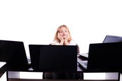 Menina bonita que senta-se em uma tabela na frente de muitos portáteis isolados Fotografia de Stock