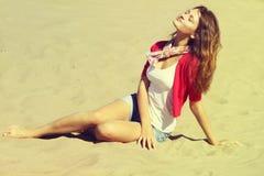 Menina bonita que senta-se na areia Fotos de Stock Royalty Free