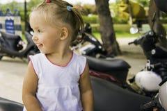 Menina bonita que senta-se na bicicleta no parque examina-o e estuda- Foto de Stock Royalty Free