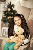 Menina bonita que senta-se na cadeira Foto de Stock Royalty Free