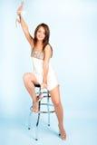 Menina bonita que senta-se na cadeira da barra Imagens de Stock Royalty Free