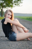 Menina bonita que senta-se na estrada Fotos de Stock Royalty Free