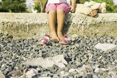 Menina bonita que senta-se na margem e nos jogos Imagem de Stock