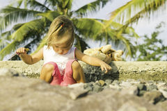 Menina bonita que senta-se na margem e nos jogos Fotos de Stock