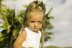 Menina bonita que senta-se na margem e nos jogos Fotografia de Stock Royalty Free