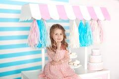 Menina bonita que senta-se na tabela com doces Barra do aniversário dos doces Retrato de um close up da cara do bebê Pouco menina foto de stock