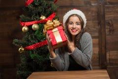 Menina bonita que senta-se na tabela com uma árvore próxima atual do ano novo Imagem de Stock