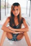 Menina bonita que senta-se na tabela concreta abaixo do para-sol Fotos de Stock Royalty Free