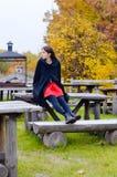 Menina bonita que senta-se na tabela de madeira velha no outono Imagens de Stock Royalty Free