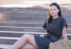 menina bonita que senta-se nas escadas foto de stock