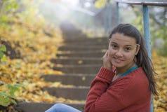 Menina bonita que senta-se nas escadas no outono Fotos de Stock