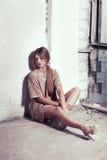 Menina bonita que senta-se no assoalho perto da janela Fotos de Stock Royalty Free