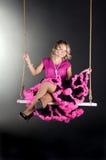 Menina bonita que senta-se no balanço Imagem de Stock