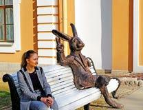 Menina bonita que senta-se no banco imagens de stock