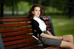 Menina bonita que senta-se no banco Imagem de Stock