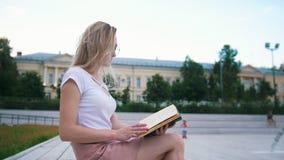 Menina bonita que senta-se no banco que lê um livro no parque urbano video estoque