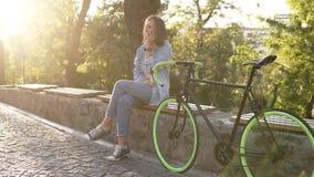 Menina bonita que senta-se no banco ou no parapeito no parque da cidade com sua bicicleta trekking ao lado dela Fala por seu móbi filme