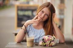 Menina bonita que senta-se no café da rua e em batidos bebendo no fundo urbano foto de stock royalty free