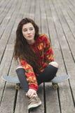 Menina bonita que senta-se no skate, conceito urbano do estilo de vida imagens de stock royalty free
