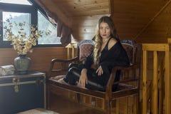 Menina bonita que senta-se no sofá fotografia de stock